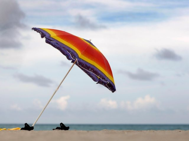 HOLLYWOOD, FL - AUGUST 19: A beach umbrella and sandals are seen on the nearly empty beach on August 19, 2009 in Hollywood, Florida. An estimated 20.1 million people visited Florida from April through June, a 9.4 percent decrease over the same period last year, Florida's tourism marketing agency reported. …