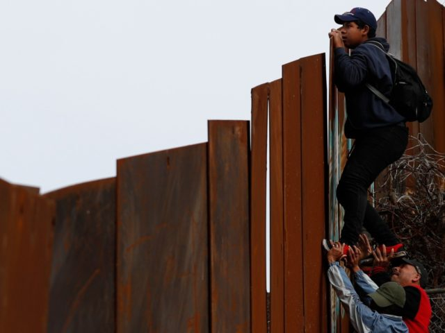 A Honduran migrant is boosted up by two friends as he jumps the U.S. border wall to surrender to U.S. Border Patrol agents waiting on the other side, in Tijuana, Mexico, Sunday, Dec. 9, 2018. Discouraged by the long wait to apply for asylum through official ports of entry, many …