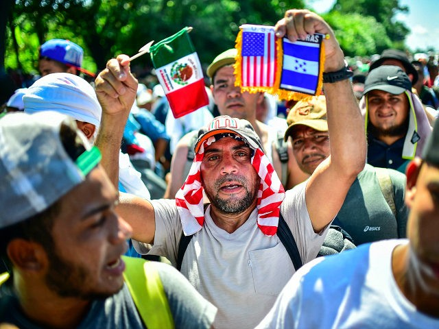 A migrant heading in a caravan to the US, holds Mexican, US and Honduran national flags on the road linking Ciudad Hidalgo and Tapachula, Chiapas state, Mexico, on October 21, 2018. - Thousands of Honduran migrants resumed their march toward the United States on Sunday from the southern Mexican city …