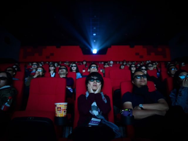 "This picture taken on April 27, 2018 shows people watching a movie at a cinema in Wanda Group's Oriental Movie Metropolis in Qingdao, China's Shandong province. - A massive ""movie metropolis"" billed as China's answer to Hollywood opened on April 28, aiming to boost the domestic film industry and attract …"