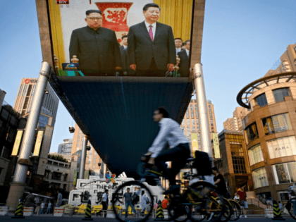 People bicycle past a giant TV screen broadcasting the meeting of visiting North Korean leader Kim Jong Un and Chinese President Xi Jinping during a welcome ceremony at the Great Hall of the People in Beijing in June.(ANDY WONG/AP)