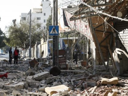 Residents gather in a debris-strewn street in Gaza City on May 5, 2019, that was hit during Israeli air strikes on the Palestinian enclave. - Gaza militants fired fresh rocket barrages at Israel early today in a deadly escalation that has seen Israel respond with waves of strikes as a …