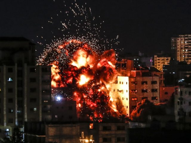 An explosion is pictured among buildings during an Israeli airstike on Gaza City on May 4, 2019. - Gaza militants fired a barrage of rockets at Israel, which responded with airstrikes, officials said, as a fragile ceasefire again faltered. (Photo by Mahmud Hams / AFP) (Photo credit should read MAHMUD …