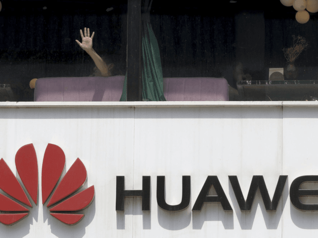 A man presses on the glass window near a logo for Huawei in Beijing on Thursday, May 16, 2019. In a fateful swipe at telecommunications giant Huawei, the Trump administration issued an executive order Wednesday apparently aimed at banning its equipment from U.S. networks and said it was subjecting the …