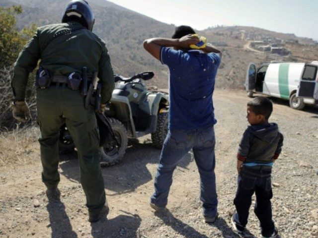 In this June 28, 2018, file photo, a Guatemalan father and son, who crossed the U.S.-Mexico border illegally, are apprehended by a U.S. Border Patrol agent in San Diego. California will introduce group trials on Monday, July 9, for people charged with entering the country illegally. Federal prosecutors in Arizona, …