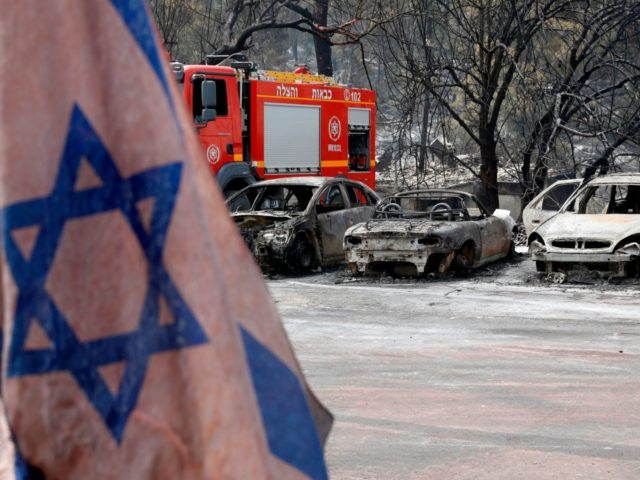 An Israeli flag is pictured in front of vehicles that were badly damaged by a fire amidst extreme heat wave in the village of Mevo Modi'im, in central Israel on May 24, 2019. (Photo by JACK GUEZ / AFP) (Photo credit should read JACK GUEZ/AFP/Getty Images)