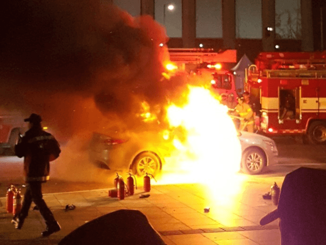 This picture taken on January 9, 2019 by eyewitness Lee Sang-ho shows a burning taxi vehicle on the road near the US embassy in central Seoul. - A South Korean taxi driver burned himself to death in protest at a ride-sharing service being introduced by the country's largest mobile chat …