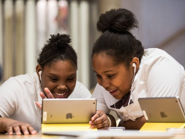 "NEW YORK, NY - DECEMBER 09: Jiavaennye Green (L) and Taylor Phillips, third grade children from PS 57 James Weldon Johnson Leadership Academy, learn how to code at an Apple Store through Apple's ""Hour of Code"" workshop program on December 9, 2015 in New York City. Tim Cook, CEO of …"
