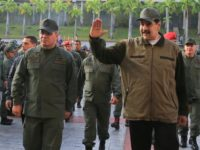 In this photo released by Miraflores Press Office, Venezuela's President Nicolas Maduro, right, accompanied by his Defense Minister Vladimir Padrino Lopez, waves upon his arrival to Fort Tiuna for a meeting with troops, in Caracas, Venezuela, Thursday, May 2, 2019. (Jhonn Zerpa/Miraflores Press Office via AP)