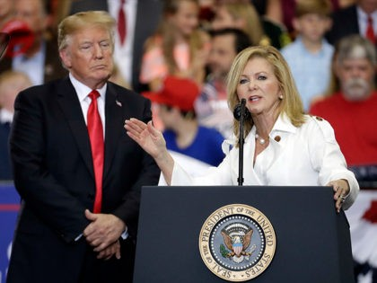 FILE - In this May 29, 2018 file photo, President Donald Trump listens as Rep. Marsha Blackburn, R-Tenn., speaks at a rally at the Nashville Municipal Auditorium in Nashville, Tenn. Blackburn is supposed to do well among Tennessee's hog farmers and whiskey makers. Yet the Republican Senate candidate is struggling …
