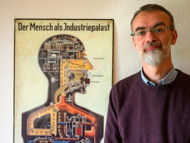 "Department head at the Institute of Anatomy of the Brandenburg Medical School (MHB) Andreas Winkelmann poses next to a poster from 1926 detailing the human body as an ""Industry Palace"", in his office in Neuruppin on April 30, 2019. - More than seven decades after the end of World War …"
