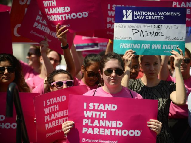 Protesters hold posters in support of Planned Parenthood at a rally to oppose the repeal of the Affordable Care Act and its replacement on Capitol Hill on June 21, 2017 in Washington, DC. Criticism is mounting on the GOP for health care reform legislation being done behind closed doors. (Photo …