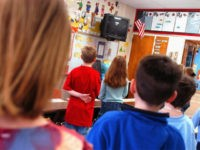 """WARMINSTER, PA - MARCH 24: First graders at Longstreth Elementary School pledge allegiance to the flag March 24, 2004 in Warminster, Pennsylvania. An atheist parent, Michael Newdow, of Sacramento, California is scheduled to be heard by the Supreme Court today to defend his position that the """"Under God"""" in the …"""