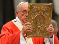 Pope Francis holds aloft the book of the gospels as he leads a mass for the imposition of the Pallium upon the new metropolitan archbishops and the solemnity of Saints Peter and Paul on June 29, 2014 at St Peter's basilica in Vatican. AFP PHOTO / VINCENZO PINTO (Photo credit …
