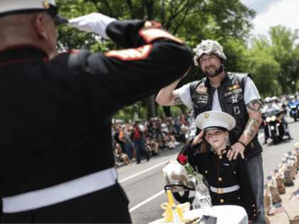 "A father takes his son wearing a Marine uniform to salute Marine Staff Sgt. Tim Chambers, ""the saluting Marine"", as they take part in the ""Rolling thunder"" parade, part of the Memorial weekend honouring war veterans in Arlington, near Washington, on May 26 2019. - Thousands of bikers converged on …"