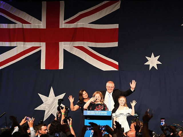 Australia's Prime Minister Scott Morrison (C on the stage) waves to his supporters following a victory speech with his family after winning the Australia's general election in Sydney on May 18, 2019. - Australia's ruling conservative coalition appeared to secure a shock election win on May 18, with the party …