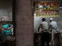 Uighur men in Kashgar make bread under a poster of Chinese leaders, including Mao Zedong and Xi Jinping, in 2017. Detainees are reportedly forced to chant patriotic songs about Xi in order to get food in detention camps.Kevin Frayer/Getty Images