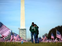 Iraq war veteran couple Colleen Ryan and Jeff Hensley of the US Navy comfort each other as they help set up 1,892 American flags on the National Mall in Washington, DC, on March 27, 2014. The Iraq and Afghanistan veterans installed the flags to represent the 1,892 veterans and service …