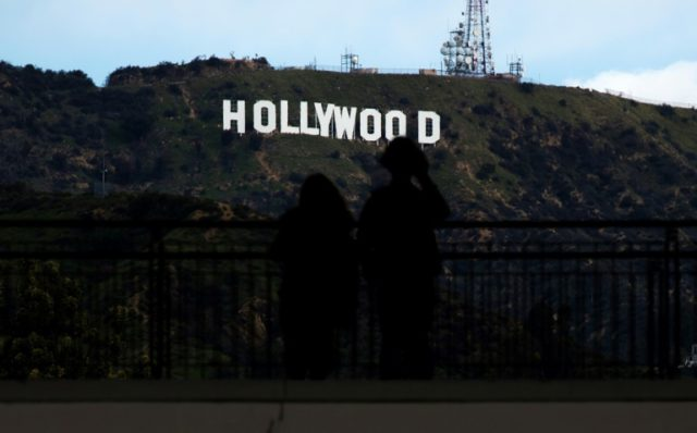 Two tourists, seen in this file photo, look at the famous sign in the hills overlooking Hollywood