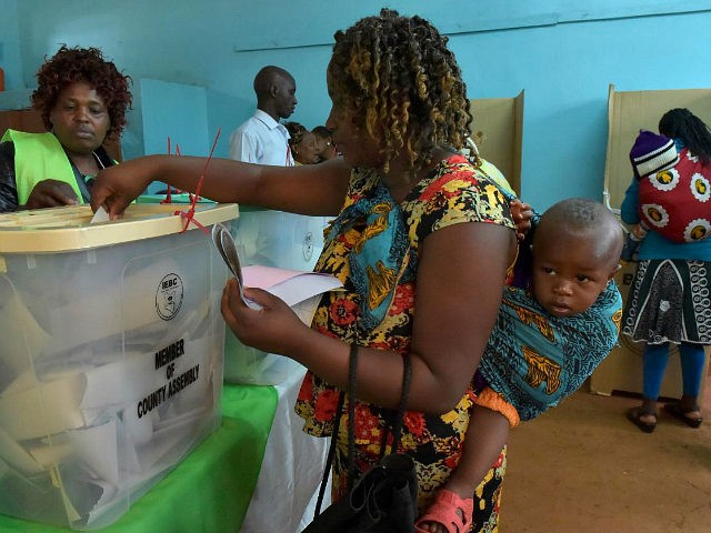 A woman carrying a baby on her back casts her ballot at a polling station in Gatundu South, Kiambu county, during general elections on August 8, 2017. Kenyans were voting on August 8 in elections headlined by a knife-edge battle between incumbent Uhuru Kenyatta and his rival Raila Odinga that …