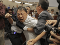 Pro-democracy lawmaker Wu Chi-wai, center, scuffles with security guards at Legislative Council on May 11. Photographer: Vincent Yu/AP