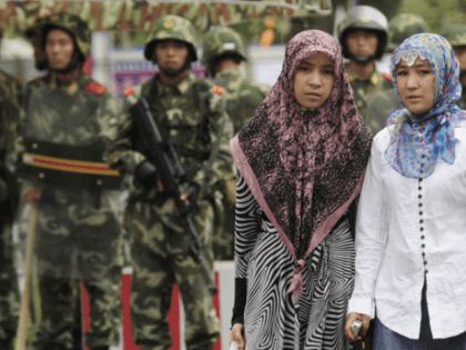Two ethnic Uighur women pass Chinese paramilitary policemen standing guard outside the Grand Bazaar in the Uighur district of the city of Urumqi in China's Xinjiang region on July 14, 2009. A mosque was closed and many businesses were shuttered a day after police shot dead two Muslim Uighurs, as …