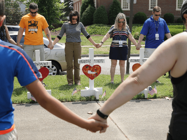 People hold hands and pray together at a makeshift memorial for the 12 victims of a mass shooting at the Municipal Center June 02, 2019 in Virginia Beach, Virginia. Eleven city employees and one private contractor were shot to death Friday in the city's operations building by engineer DeWayne Craddock …
