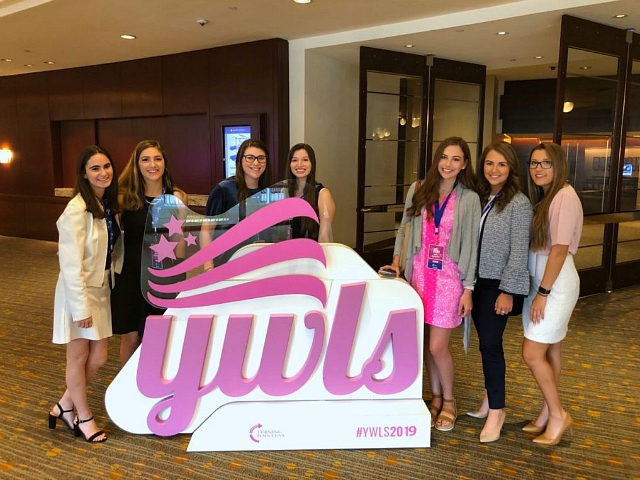 Event attendees pose for a photo in front of a YWLS sign. (Alana Mastrangelo/Breitbart News)