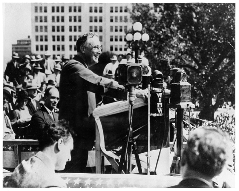 "Franklin D. Roosevelt giving a campaign speech to farmers in Topeka, Kansas, promising them a ""new deal."" Also pictured is James Roosevelt (to the left.)"