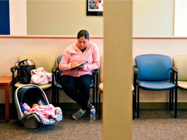 A woman fills out paperwork while waiting in a doctor's office.