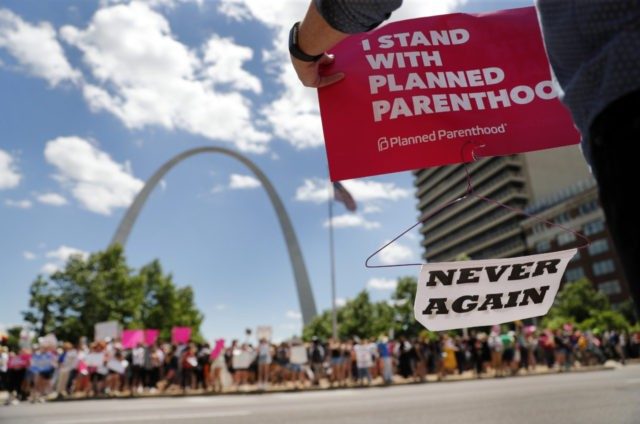 Abortion-rights supporters stand on both sides of a street near the Gateway Arch as they take part in a protest in favor of reproductive rights Thursday, May 30, 2019, in St. Louis. A St. Louis judge heard an hour of arguments Thursday on Planned Parenthood's request for a temporary restraining …