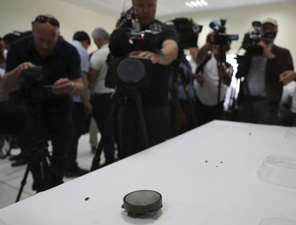 "Journalists take pictures of a magnet the U.S. Navy says came from a limpet mine that didn't explode on a Japanese-owned oil tanker at a 5th Fleet base, during a trip organized by the Navy for journalists, near Fujairah, United Arab Emirates, Wednesday, June 19, 2019. Cmdr. Sean Kido of the U.S. Navy's 5th Fleet said Wednesday that the limpet mine used on a Japanese-owned oil tanker last week ""bears a striking resemblance"" to similar Iranian mines. (AP Photo/Kamran Jebreili)"