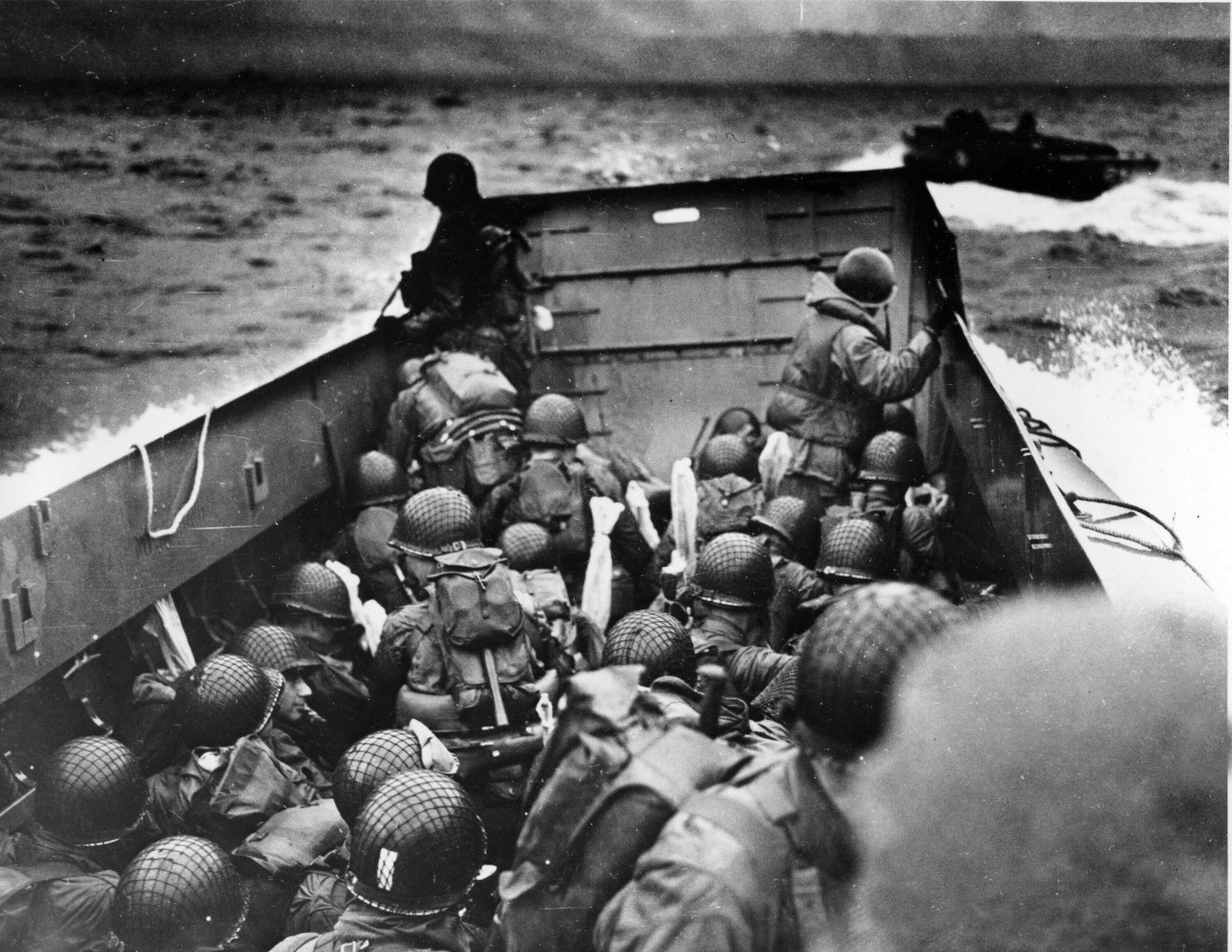 In this photo provided by the U.S. Coast Guard, a U.S. Coast Guard landing barge, tightly packed with helmeted soldiers, approaches the shore at Normandy, France, during initial Allied landing operations, June 6, 1944. These barges ride back and forth across the English Channel, bringing wave after wave of reinforcement troops to the Allied beachheads. (AP Photo/U.S. Coast Guard)