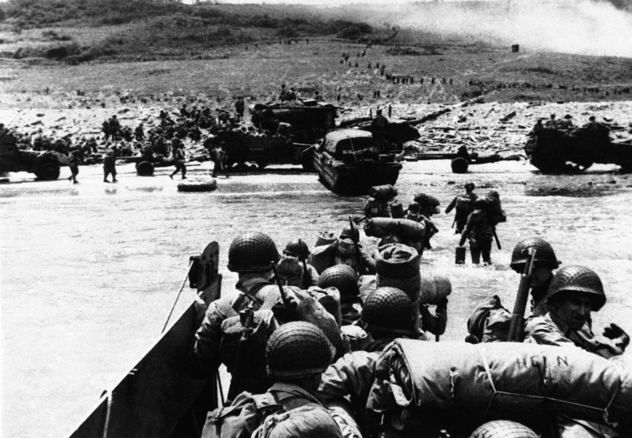 """""""Ducks"""" (amphibious trucks) and a half-track follow foot troops ashore during opening of invasion of France on a 100-mile front along the Normandy coast by Allied force on June 6, 1944. (AP Photo)"""