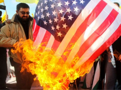 Lebanese supporters of the Shiite Hezbollah movement burn a US flag during a rally against the US president's decision to recognise Jerusalem as the capital of Israel, on January 28, 2018, in the southern Lebanese village of Alma al-Shaab, on the border with Israel. / AFP PHOTO / Mahmoud ZAYYAT …