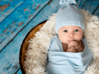 Little baby boy with knitted hat in a basket, happily smiling - stock photo Little baby boy with knitted hat in a basket, happily smiling and looking at camera, isolated studio shot