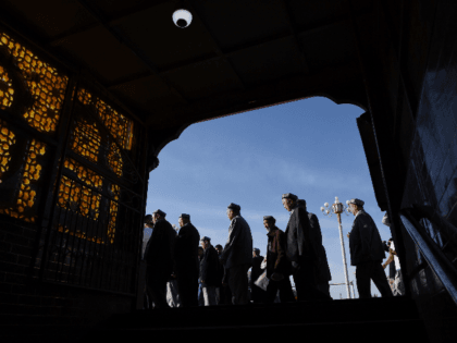Uighur men make their way past a subway entrance after Eid al-Fitr prayers, marking the end of Ramadan, at the Id Kah mosque in Kashgar, in China's western Xinjiang region early on June 5, 2019. - While Muslims around the world celebrated the end of Ramadan with early morning prayers …