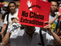 TOPSHOT - A protester marches with a placard during a rally against a controversial extradition law proposal in Hong Kong on June 9, 2019. - Huge protest crowds thronged Hong Kong on June 9 as anger swells over plans to allow extraditions to China, a proposal that has sparked the …