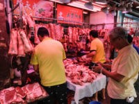 A customer waits as butchers prepare pork meat at a market in Hong Kong on May 11, 2019. - Hong Kong will cull 6,000 pigs after African swine fever was detected in an animal at a slaughterhouse close to the border with China, the first case of the disease in …