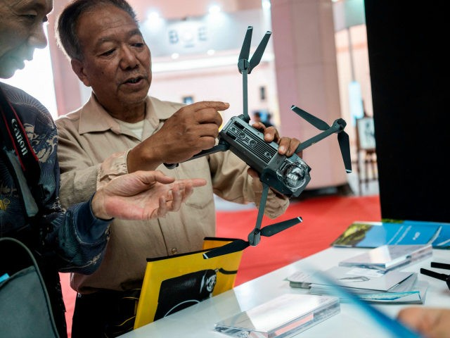 Visitors look at a drone from the Chinese company DJI at the Beijing Photo fair on May 4, 2018. (Photo by FRED DUFOUR / AFP) (Photo credit should read FRED DUFOUR/AFP/Getty Images)