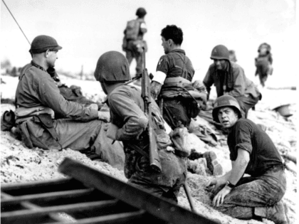 ** FILE ** In this June 6, 1944 file photo, first wave beach battalion Ducks lay low under the fire of Nazi guns on the beach of southern France on D-Day, June 6, 1944 during World War II. One invader operates a walkie talkie radio directing other landing craft to …