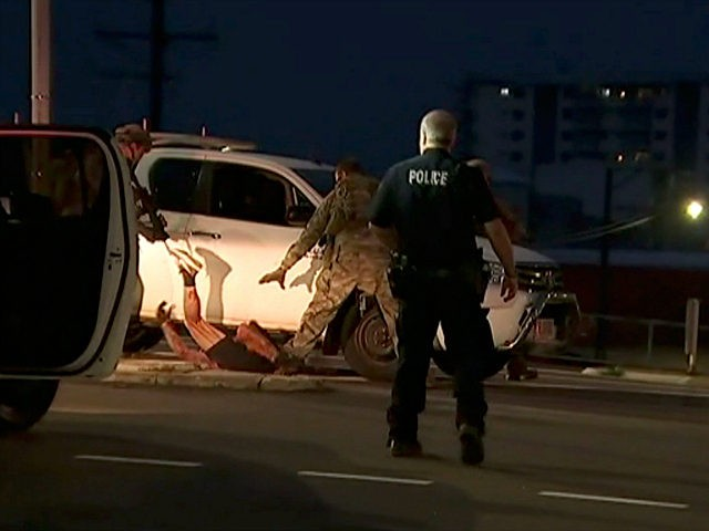 In this image made from video, police proceed to apprehend a suspect on the ground next to a white truck, Tuesday, June 4, 2019, in Darwin Australia. Media reports say a gunman has killed at least four people in the Australian city of Darwin. Northern Territory Police Duty Superintendent Lee …