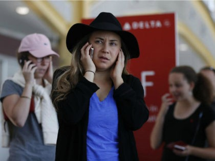 Jenna Raspanti and other travelers talk on their cell phones as they stand in line at the Delta ticketing counter at Washington's Ronald Reagan Washington National Airport, Monday, Aug. 8, 2016. Raspanti is trying to get to San Francisco after her Delta flight was delayed. Delta Air Lines delayed or …