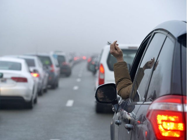A man smokes a cigarette at his car's window as holiday-makers drive at slow pace on the A40 towards Geneva near Lyon, Central eastern France, on February 21, 2015, as snow made access difficult towards the Alps on February 21, with an estimated 4 to 5 hours to access ski …