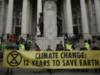 FILE - In this Thursday, April 25, 2019 file photo, Extinction Rebellion climate change protesters hold up a banner near the Bank of England, in the City of London. The environmental activist group Extinction Rebellion has postponed a plan to shut down London's Heathrow Airport with drones after it was …