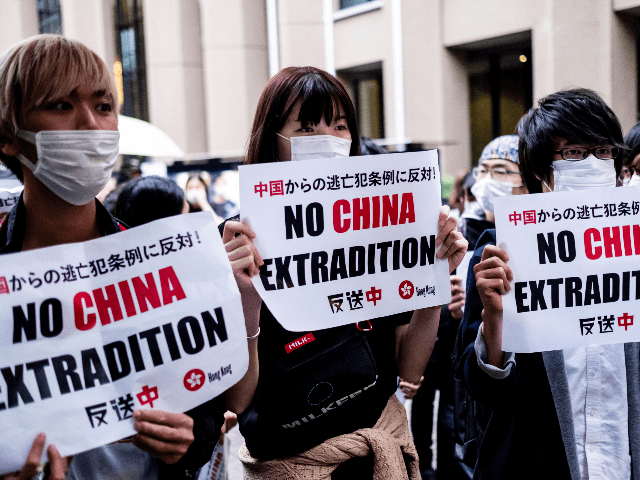 Foreign students In Japan hold up a placard which says No China Extradition at Meiji University on June 12, 2019 in Tokyo, Japan. Students gathered in Meiji University to show their support as Hong Kong braced for another mass rally in a show of strength against the government over a …