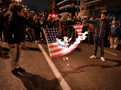 Protesters burn a US flag during an annual demonstration gathering to American embassy, commemorating the 1973 student uprising that helped topple Greece's US-backed junta, in the center of Athens on November 17, 2018. - At least 44 people were killed in the 1973 military crackdown on the student uprising at …