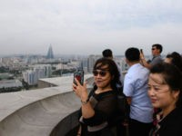 Tourists take photos from a viewing deck of the Juche tower in front of the city skyline of Pyongyang on September 6, 2018. - North Korea is preparing to mark the 70th anniversary of its founding on September 9. (Photo by Ed JONES / AFP) (Photo credit should read ED …