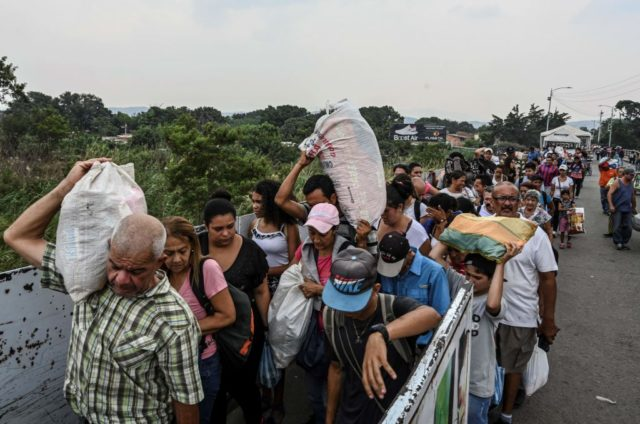 """People carry goods as they cross the international border bridge """"Simon Bolivar"""" from the Colombian city of Cucuta back to San Antonio del Tachira in Venezuela, on April 13, 2019. - US Secretary of State Mike Pompeo, who is on a four-nation tour of Latin American allies, will finish his …"""