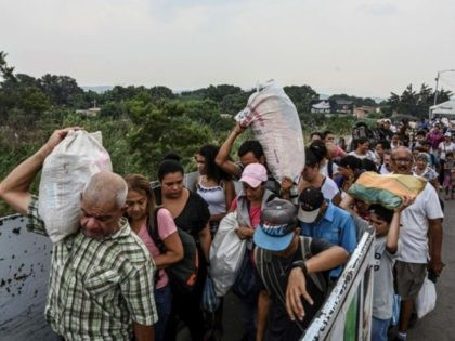 "People carry goods as they cross the international border bridge ""Simon Bolivar"" from the Colombian city of Cucuta back to San Antonio del Tachira in Venezuela, on April 13, 2019. - US Secretary of State Mike Pompeo, who is on a four-nation tour of Latin American allies, will finish his …"